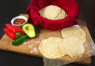 Homemade flour tortillas with a side of salsa and vegetables