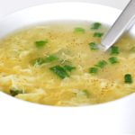 Close up of a silver spoon and white bowl containing egg drop soup.