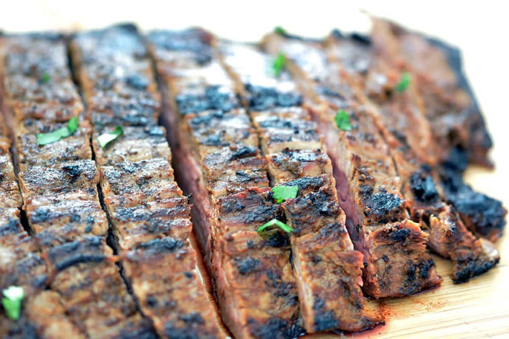 Up close shot of grilled flank steak sliced to make carne asada recipes.