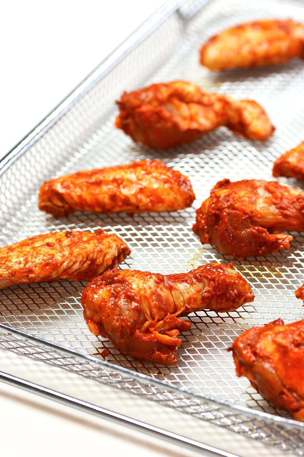 Raw chicken wings on an air fryer basket
