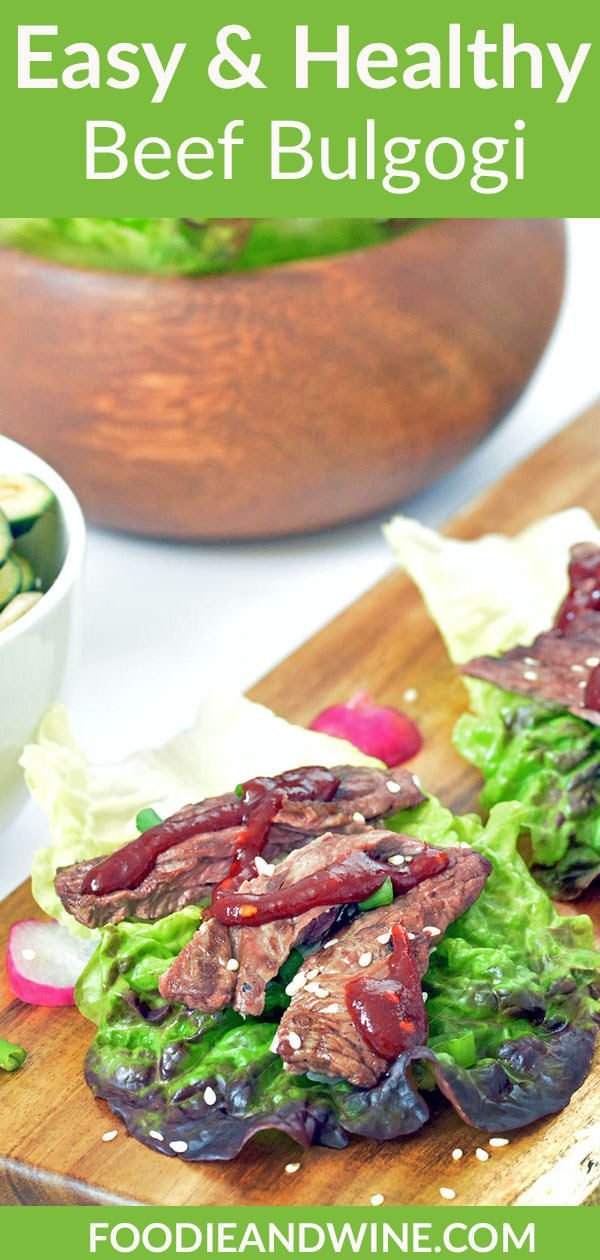 Close up of Cooked Beef Bulgogi in a lettuce cup on a wood platter.