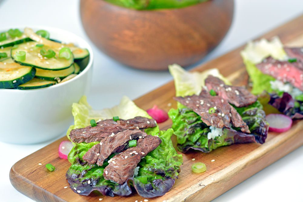Cooked Beef Bulgogi in a lettuce cup on a wood platter.