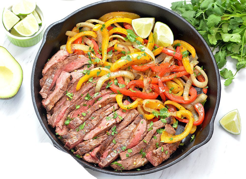 Steak Fajitas and onions and peppers in a black cast iron pan