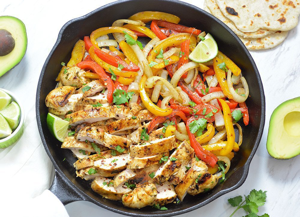 Chicken Fajitas with bell peppers and onions in a black cast iron pan