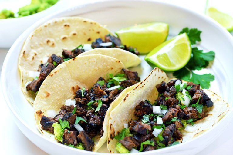 Three Carne Asada tacos topped with cilantro and onions on a white plate. Served with lime slices and cilantro.