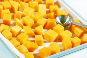 Fresh cut butternut squash covered in olive oil and spread out on a silver cookie sheet