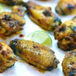 Baked Chicken Wings rubbed with a dry Jamaican Jerk Seasoning, on crinkled white parchment papers. Served with slices of lime.