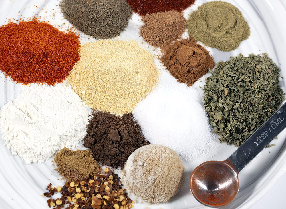 14 different Ingredients to make Jerk Seasoning on a white plate.
