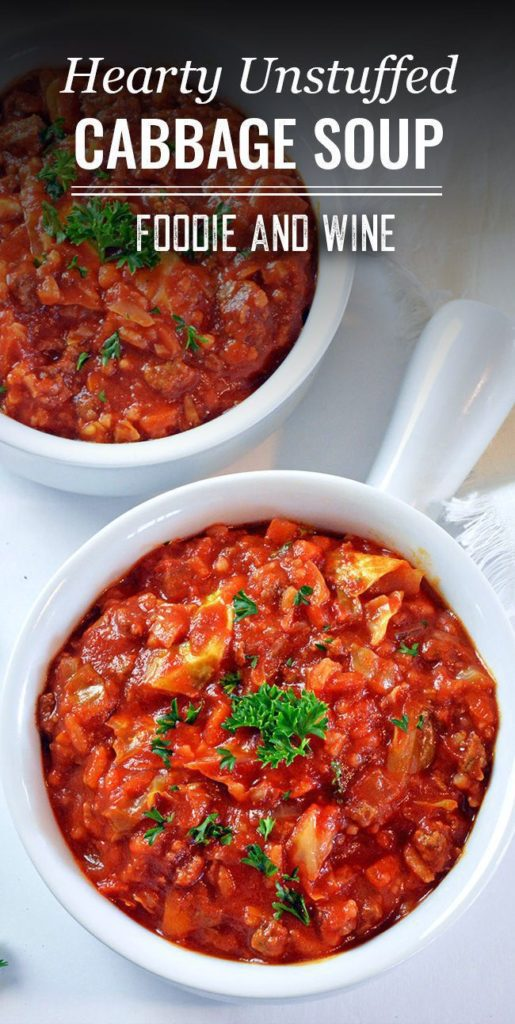 Two white bowls full of red unstuffed cabbage soup topped with green parsley.