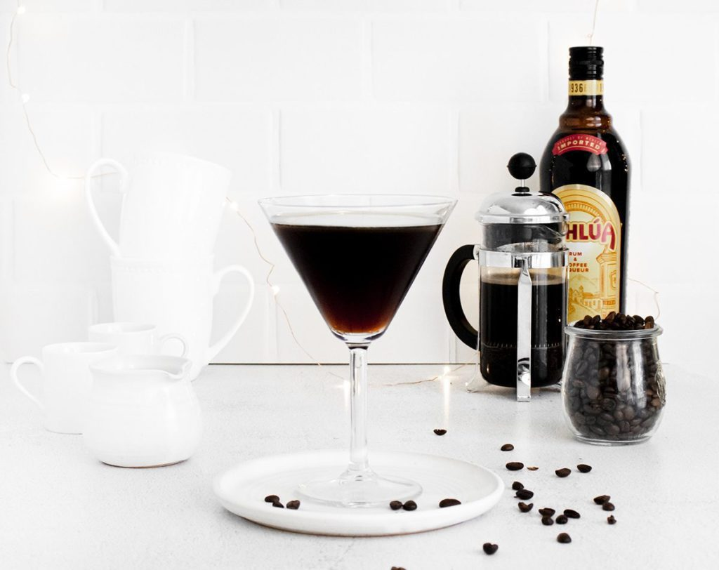 Hazelnut Espresso Martini in a martini glass on a white plater. A bottle of Kahlua and coffee press are in the background;