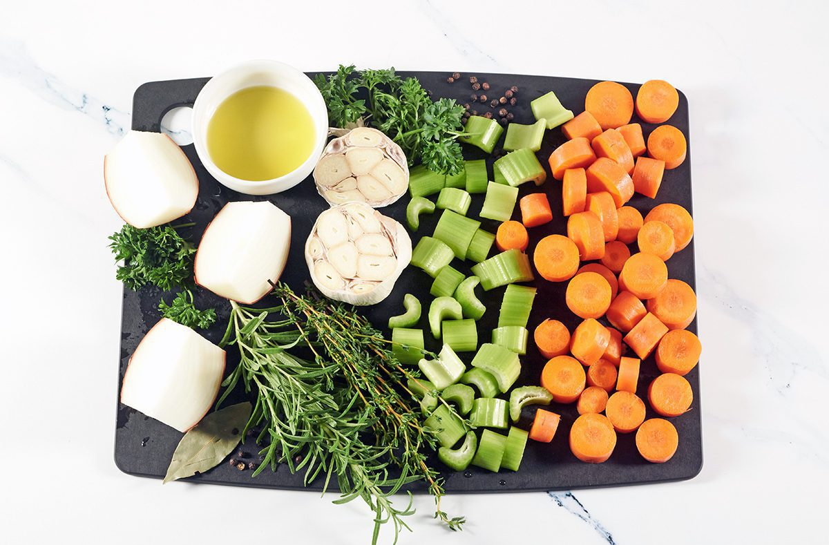 Picture of all the ingredients used to make bone broth on a black cutting board. Ingredients include onions, carrots, celery, pepper, rosemary, thyme, parsley and garlic.