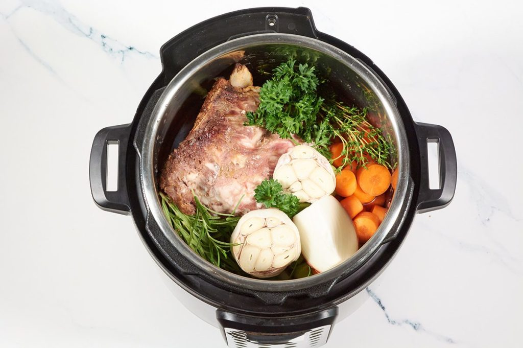 An instant pot filled with ingredients to make homemade bone broth. Pictured ingredients include beef bones, parsley, onion, garlic and carrots.