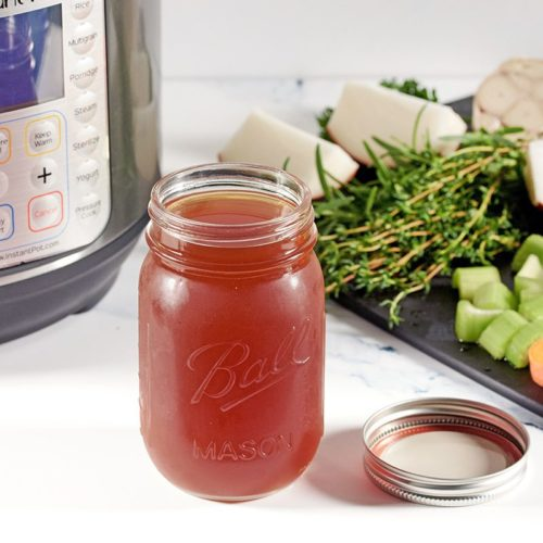 Picture of bone broth in a glass mason jar flanked by an Instant Pot machine and cut vegetables including carrots, celery, onions and garlic.