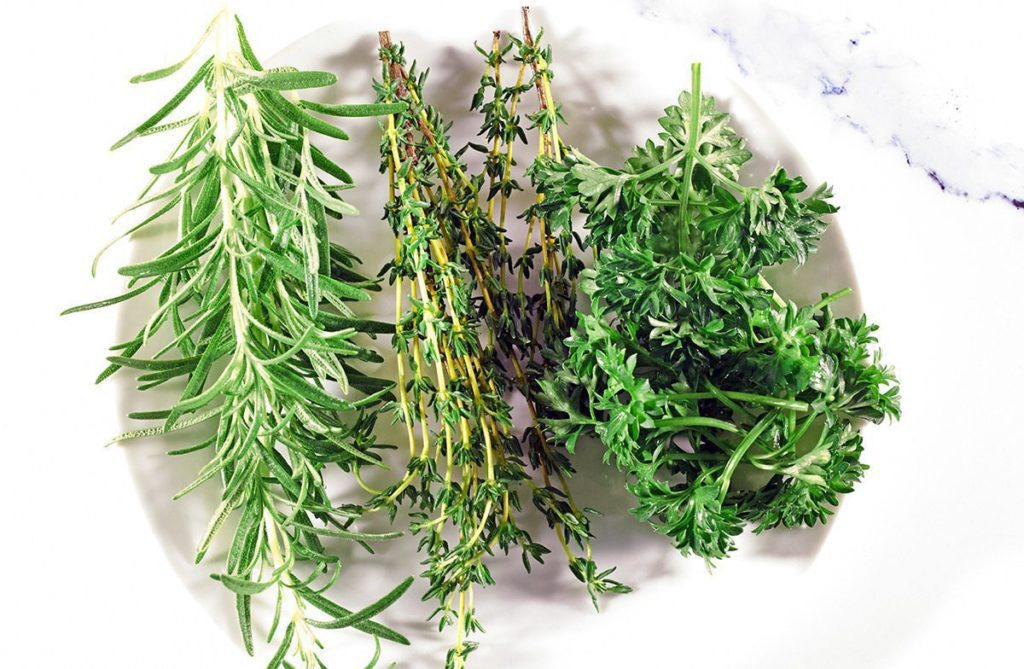 Picture of fresh rosemary, thyme and parsley on white plate.