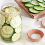 A glass mason jar full of sliced cucumbers and smashed garlic cloves to make picked cucumbers. Wooden cutting board with sliced cucumbers and bowl of sugar and salt in the background.