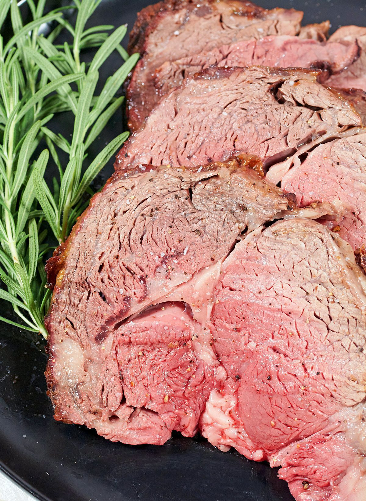 Photo of cooked prime rib slices on a black plate