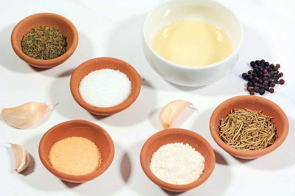 Small clay bowls of a variety of spices for Prime Rib Bub. Spices include black pepper, salt, thyme, rosemary, garlic, garlic powder and onion powder.