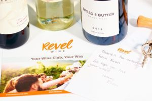 Picture of three wine bottles, a wine opener and Revel Wine Club welcoming paperword.