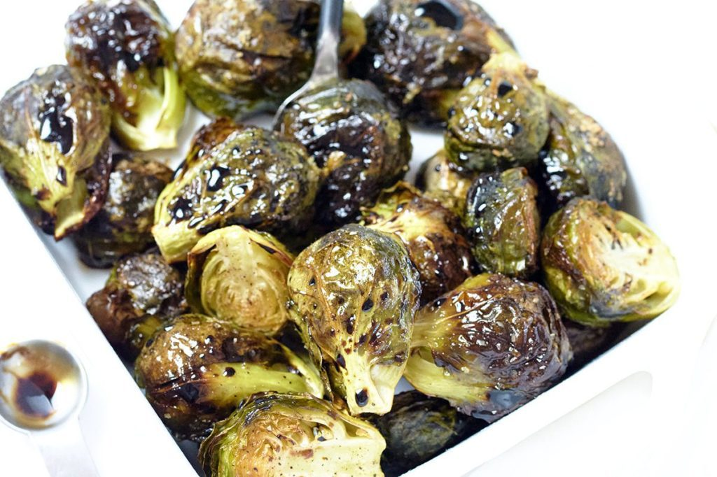 Balsamic Glazed Brussel Sprouts in a white bowl with a silver measuring spoon next to it.