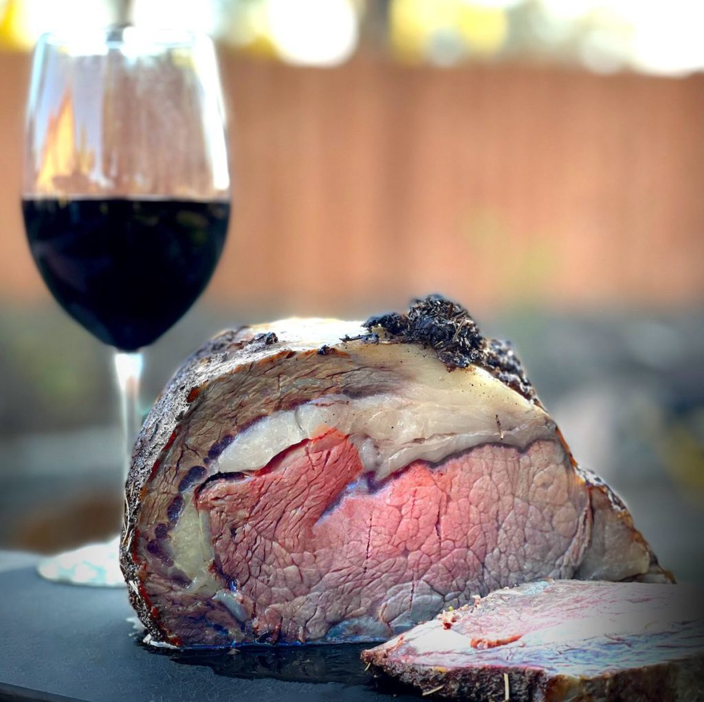 A smoked prime rib roast with one slice cut off laying on a black cutting board. A glass of red wine is setting next to the cutting board.