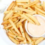 white Plate of air fried frozen french fries with chipotle mayo dipping sauce on the side.