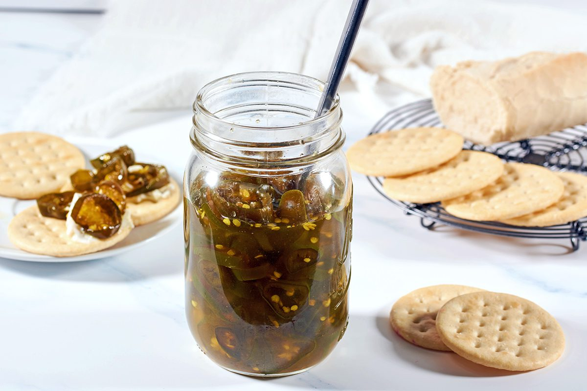A mason jar full of cowboy candy surrounded by crackers, bread and a white napkin.