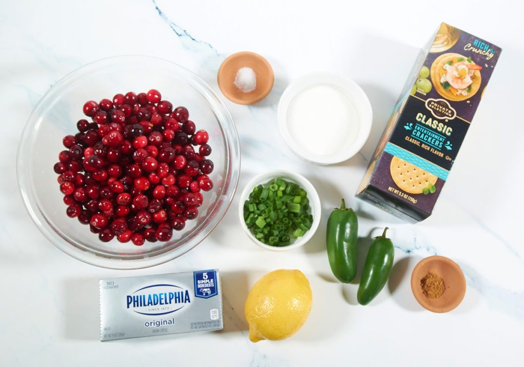 Ingredients to make cranberry jalapeno dip: cranberries, cream cheese, lemon, green onions, jalapenos, spices and crackers