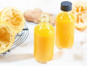 Close up of two small glass bottle holding ginger and turmeric juice. Squeezed fresh lemons off to the side.