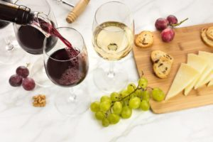 Top down view of a cheese board with a variety of cheeses, crackers and fruit along with a few glasses of red and white wine.