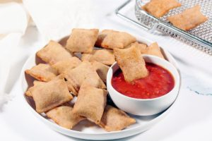 Air Fryer Pizza Rolls on a white plate with a bowl of marinara sauce. The air fryer basket is in the background.