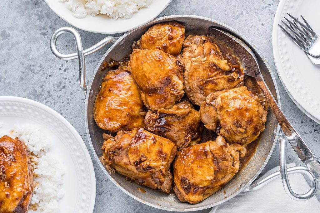 Filipino Chicken plated on a silver platter surrounded by white rice and white plates and forks.