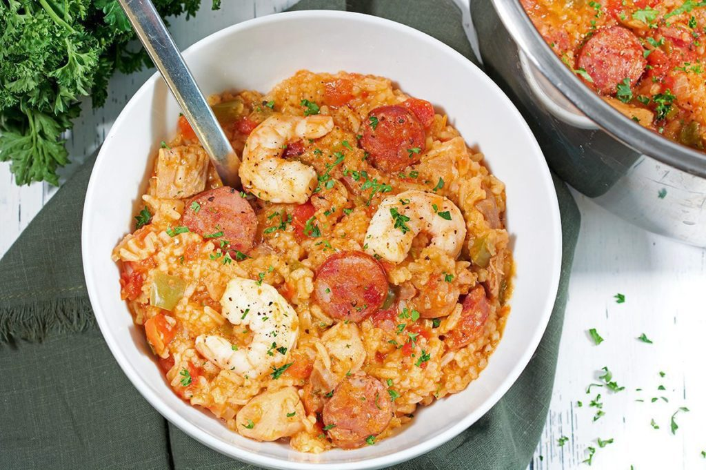 Instant Pot Jambalaya in a white bowl with a silver spoon.