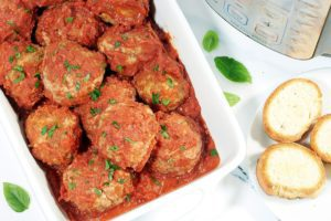 Cooked instant pot meatballs in a white casserole dish next to an instant pot and three slices of french bread.