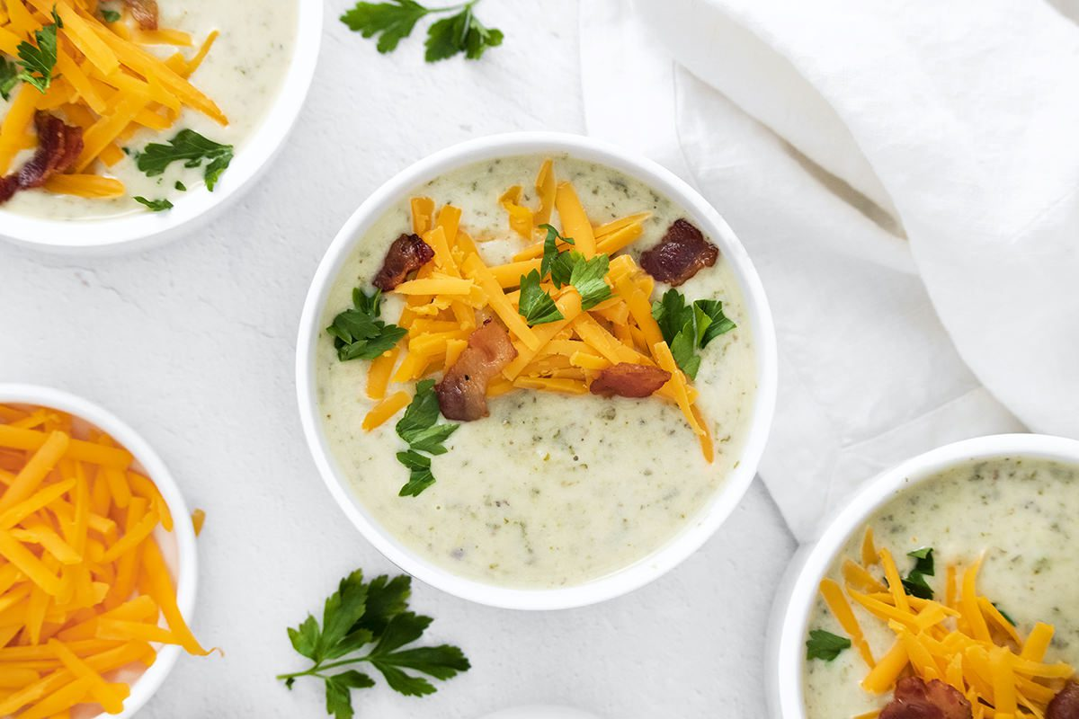 three white bowls filled with Irish Potato Soup topped with cheese and bacon.