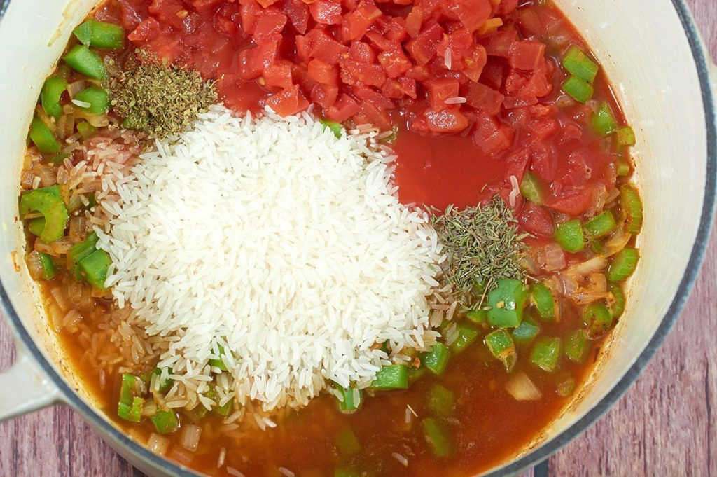 Jambalaya Ingredients un-mixed in a cream dutch oven.