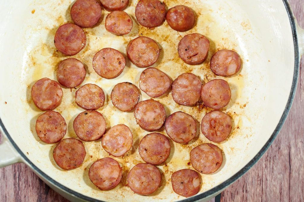 Cooked sliced sausage in a cream dutch oven.