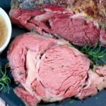 Close up picture of rare prime rib sliced on a black cutting board. Au jus is next to it in a white cup.