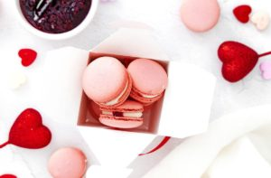 Strawberry Macrons in a to-go white box surrounded by heart shaped plastic toys and a white cup of strawberry jam.