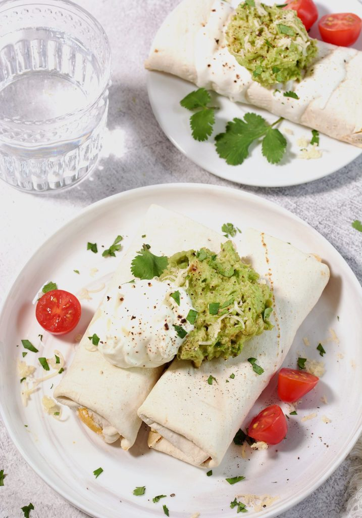 Two frozen burritos in Air Fryer topped with guacamole, sour cream, tomatoes and cilantro on a white plate. A smaller white plate with one burrito topped with guacamole is nearby as is a clear glass full of water.