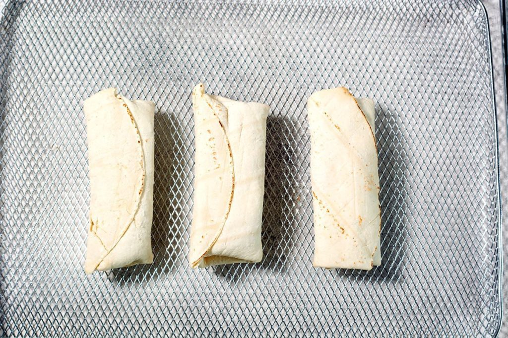 Close up of three uncooked frozen burritos on a silver air fryer rack.