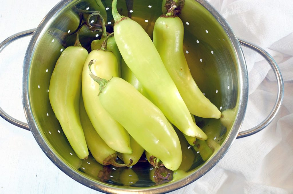 Banana Peppers in a silver colander.