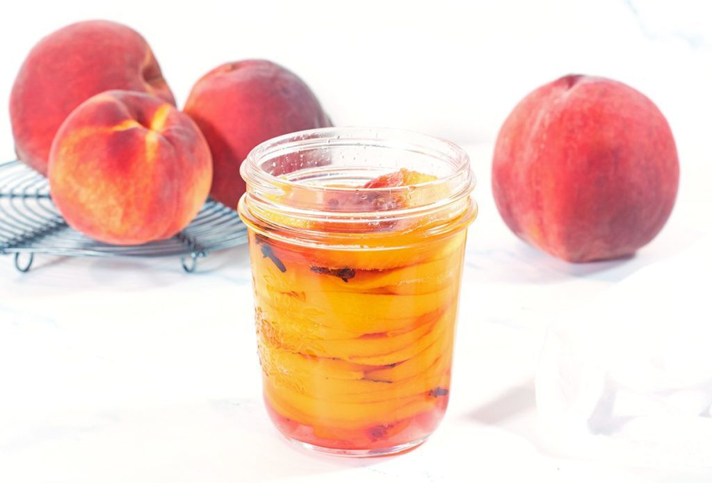 Pint size mason jar filled with pickled peaches resting on a white napkin. Four whole fresh peaches are in the background.