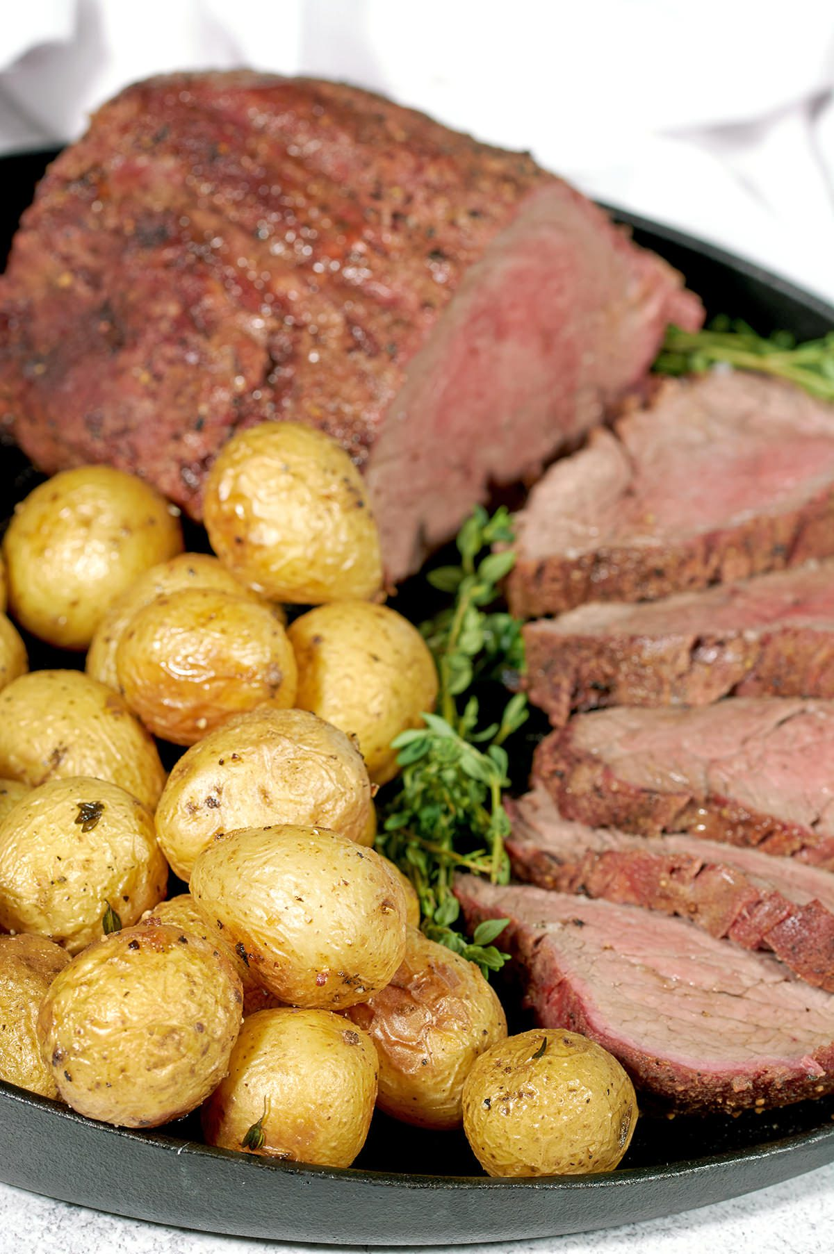 Air Fryer Baby Potatoes on a black cast iron pan along with a smoked beef tenderloin.
