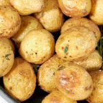 Close up shot of gold air fryer baby potatoes in a black cast iron pan with a sprig of rosemary.