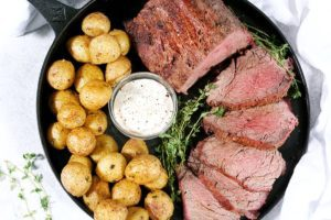 Top down view of a smoked beef tenderloin roast cut into 5 medallions. Served alongside baby potatoes and horseradish sauce on a black cat iron pan.