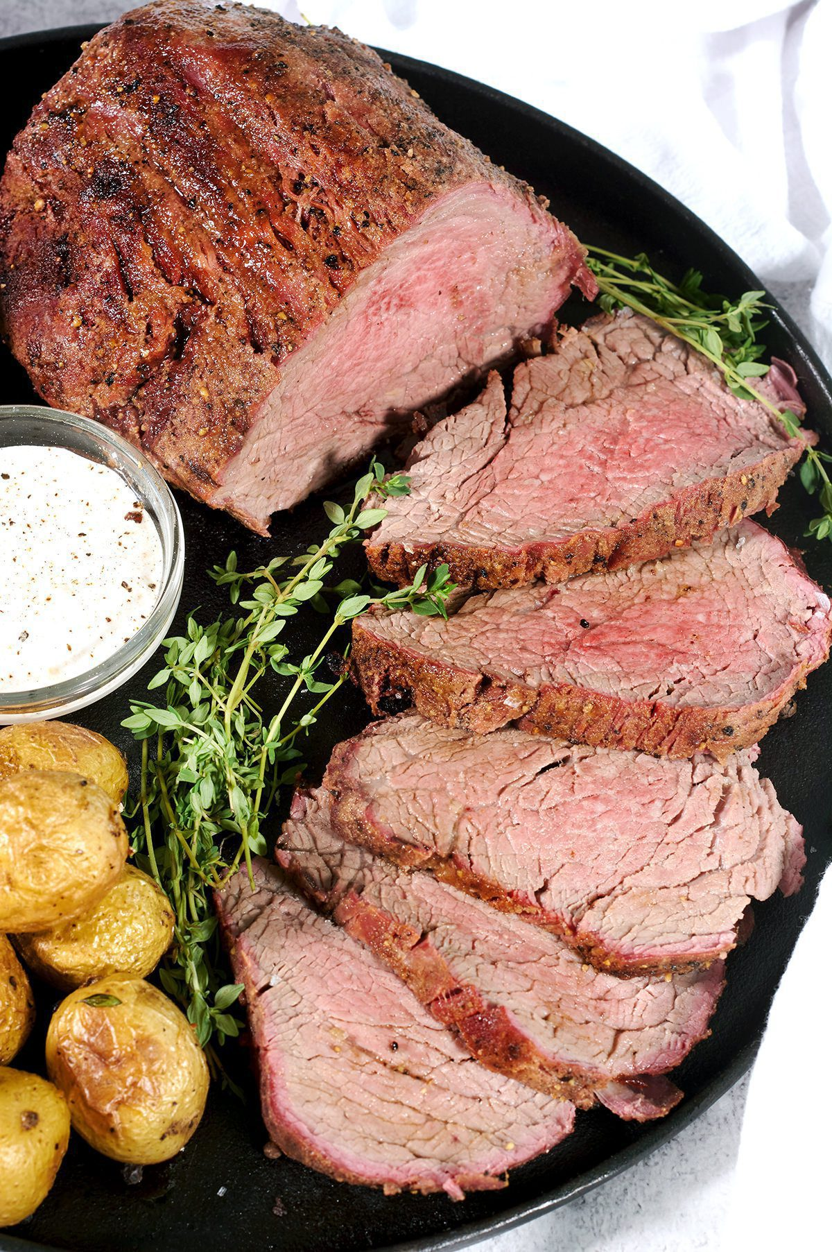 Side view of a smoked beef tenderloin cut into steaks. Accompanied by thyme, potatoes and horseradish sauce.