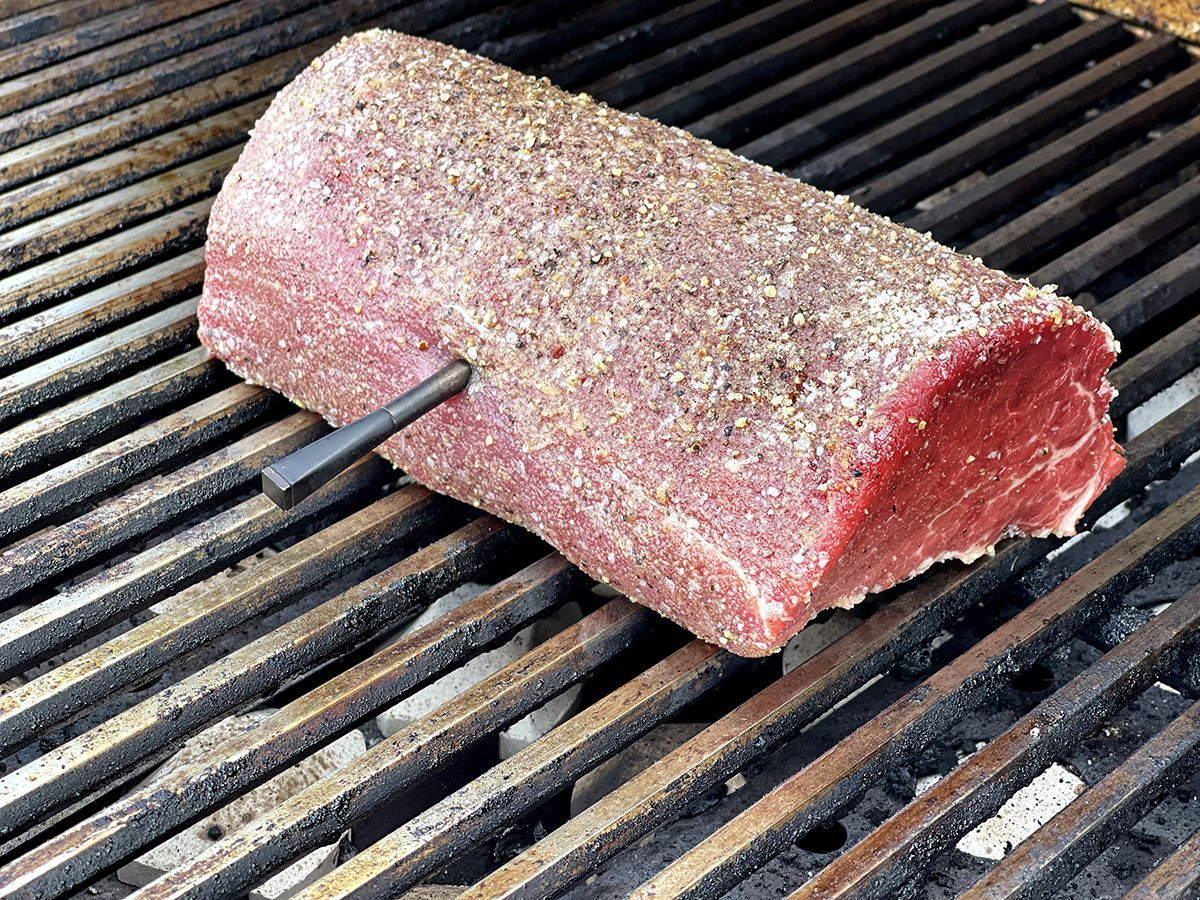Side view of a rare beef roast on a grill. A metal thermometer is sticking out of the side.