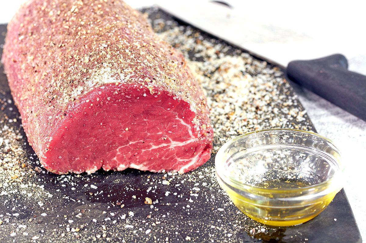 Front view of an uncooked roast covered in seasonings. A clear cup of oil is in the foreground. Before it becomes smoked beef tenderloin.